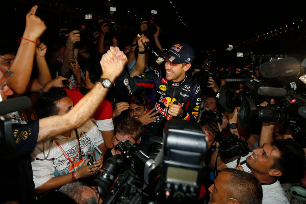 Buddh International Circuit, New Delhi, India. Sunday 27th October 2013. Sebastian Vettel, Red Bull Racing, 1st position, celebrates with fans after securing fourth drivers world title. World Copyright: Charles Coates/LAT Photographic. ref: Digital Image _N7T5908
