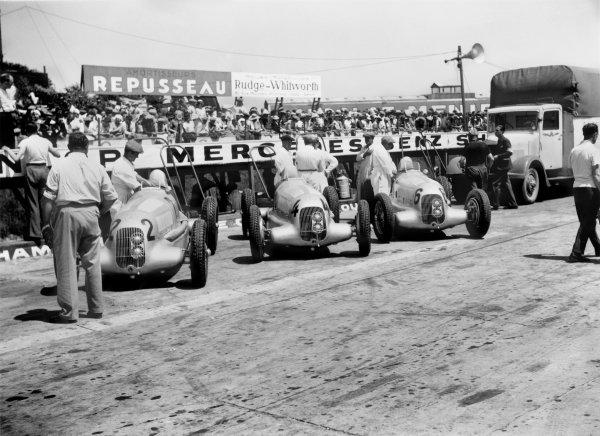 1935 French Grand Prix.Montlhery, France. 23 June 1935.The Mercedes-Benz W25B cars of Rudolf Caracciola, Manfred von Brauchitsch and Luigi Fagioli in the pits, atmosphere.World Copyright: LAT PhotographicRef: Motorsport b&w negative