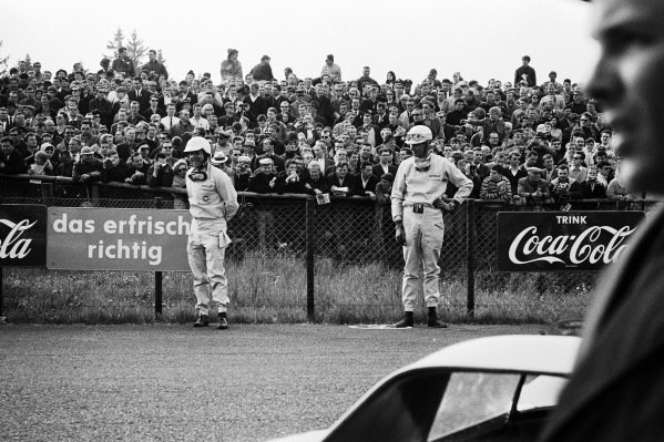 Phil Hill stands alongside Mike Parkes before they run to their cars for the start of the race.