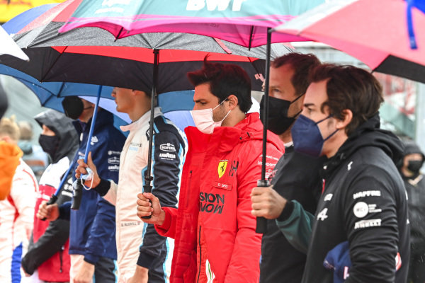 Carlos Sainz, Ferrari, Sebastian Vettel, Aston Martin, Fernando Alonso, Alpine F1, and the other drivers stand for the national anthem prior to the start