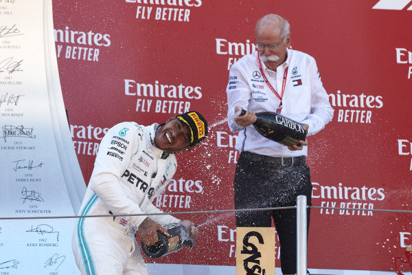 Lewis Hamilton, Mercedes AMG F1, 1st position, and Dr Dieter Zetsche, CEO, Mercedes Benz spray Champagne on the podium