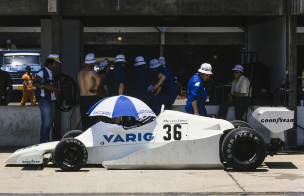 Riccardo Patrese sits under an umbrella in his Arrows FA1 Ford in the pitlane.