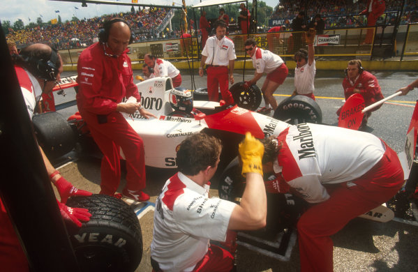 1991 San Marino Grand Prix.Imola, Italy.26-28 April 1991.Gerhard Berger (McLaren MP4/6 Honda) takes a pitstop on the way to 2nd position. McLaren team co-ordinator Jo Ramirez oversees the pitstop, with team manager David ryan behind.Ref-91 SM 06.World Copyright - LAT Photographic