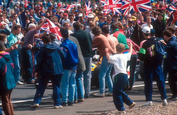 1992 British Grand Prix.Silverstone, England.10-12 July 1992.When Nigel Mansell (Williams FW14B Renault) 1st position, drove around on his victory lap the fans invaded the track as Mansell mania hit its peak. Track stewards tried in vain at the finish to hold them back and keep them from running into the way of the cars.Ref-92 GB 30.World Copyright - LAT Photographic