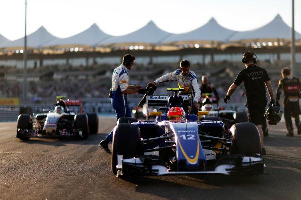 Yas Marina Circuit, Abu Dhabi, United Arab Emirates. Sunday 29 November 2015. Felipe Nasr, Sauber C34 Ferrari, and Carlos Sainz Jr, Toro Rosso STR10 Renault, arrive on the grid. World Copyright: Charles Coates/LAT Photographic ref: Digital Image _99O1702