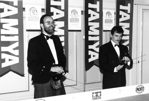 1989 Autosport Awards. Cafe Royal, London, England. 4th January 1990. Peter Foubister and Barry McGuigan play with the remote controls cars set up by Tamiya, portrait.  World Copyright: LAT Photographic. Ref: B/W Print.
