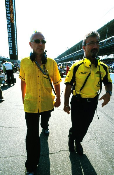 Team owner Eddie Jordan (IRE), right, walks with former Sex Pistol John Lydon, aka Johnny Rotten (GBR), left, on the Indy grid.