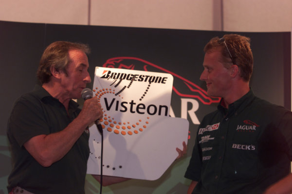 Sepang, Kuala Lumpur, Malaysia.20-22 October 2000.Jaguar Director Jackie Stewart presents Johnny Herbert with a signed rear wing endplate to celebrate his last Grand Prix.World Copyright - LAT Photographicref: digital image