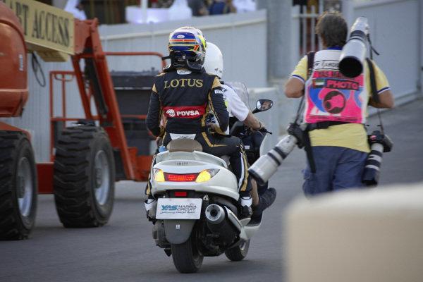 Pastor Maldonado, Lotus, on the back of the a moped.
