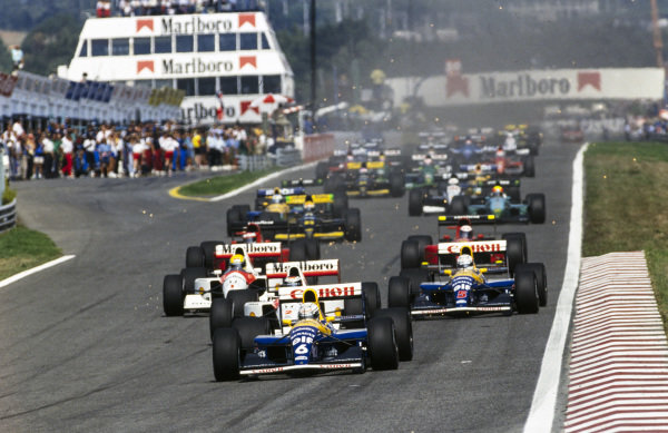 Riccardo Patrese, Williams FW14 Renault, leads Gerhard Berger, McLaren MP4-6 Honda, as Nigel Mansell, Williams FW14 Renault, and Ayrton Senna, McLaren MP4-6 Honda, lead the chasing pack.