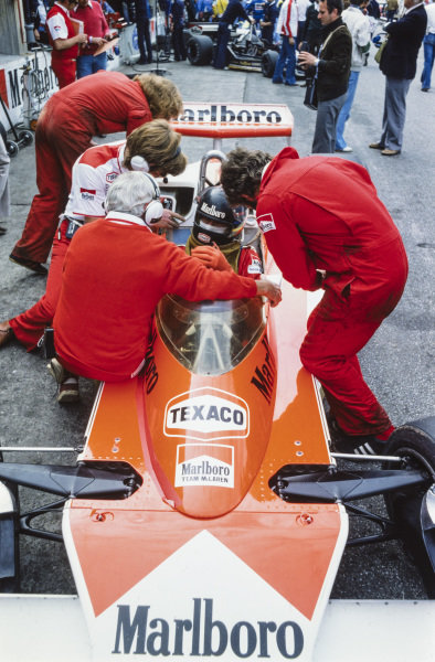 James Hunt talks to Teddy Mayer and Alastair Caldwell while seated in his McLaren M23 Ford.