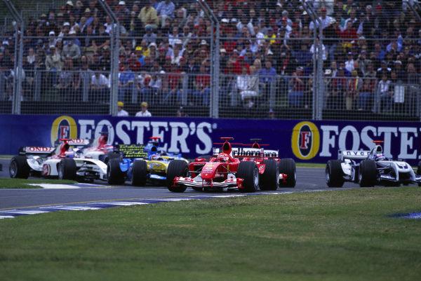 Michael Schumacher, Ferrari F2004, leads Rubens Barrichello, Ferrari F2004, Fernando Alonso, Renault R24, Jenson Button, BAR 006 Honda, Jarno Trulli, Renault R24, and Takuma Sato, BAR 006 Honda, at the start. Juan Pablo Montoya, Williams FW26 BMW, is taking to the grass.