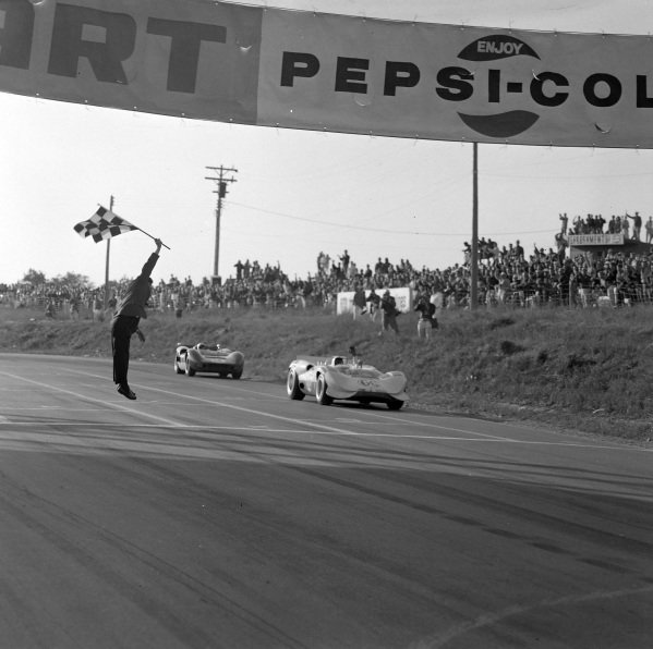 Jim Hall, Chapparal 2A Chevrolet, leads Bruce McLaren, McLaren Elva Mk II Oldsmobile, as they cross the finish line and take the chequered flag.