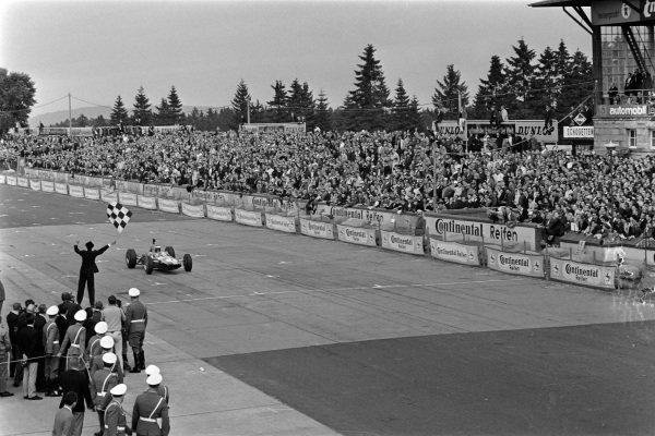 Jim Clark, Lotus 33 Climax, raises his hand in triumph as he takes the chequered flag for victory.