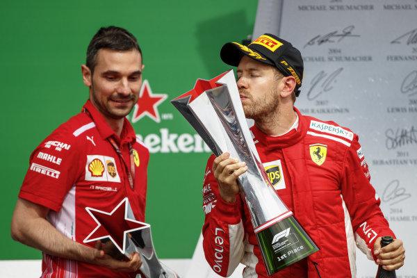 Sebastian Vettel, Ferrari, 1st position, kisses his trophy on the podium alongside Nicola Bariselli, Race Engineer, Ferrari.