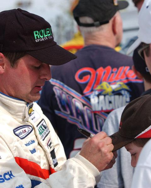 2003 Watkins Glen 6Hr. Grand Am, Watkins Glen International, Watkins Glen, N Y. U.S A.June 20-22, 2003Scott Goodyear signing a kids hat after the ceremony.C: 2003, Douglas Phillips, USALat Photographic