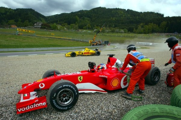 Rubens Barrichello (BRA) Ferrari F2002 climbs from his car as Giancarlo Fisichella (ITA) Jordan Honda EJ12 spins into the gravel in sympathy.