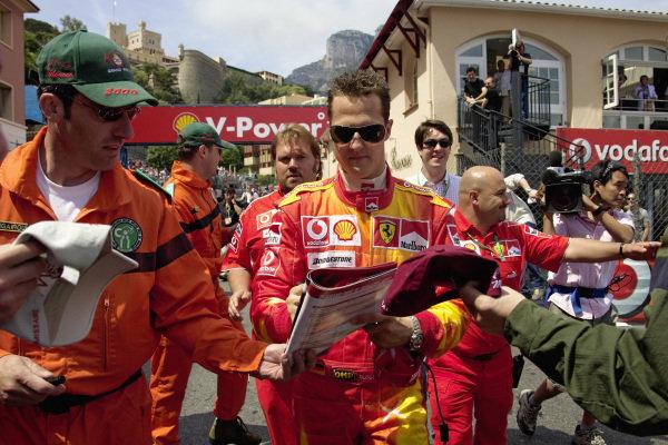 Michael Schumacher signing autographs for marshals.