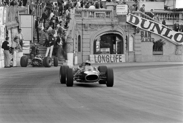 Denny Hulme, Brabham BT20 Repco, passes Jim Clark's retired Lotus 33 Climax.