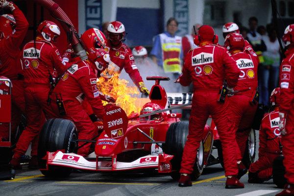Michael Schumacher's Ferrari F2003-GA, catches fire during a pitstop.