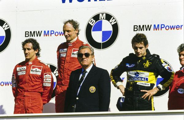 Niki Lauda, 1st position, Alain Prost, 2nd position, Ayrton Senna, 3rd position, and Jean-Marie Balestre on the podium.