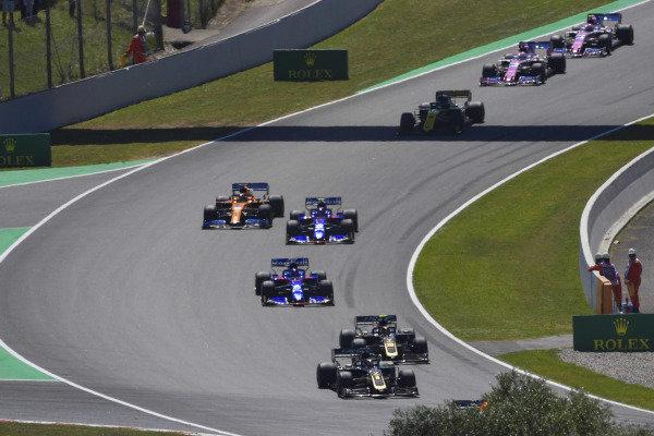Romain Grosjean, Haas VF-19, leads Kevin Magnussen, Haas VF-19, Daniil Kvyat, Toro Rosso STR14, Alexander Albon, Toro Rosso STR14, and Carlos Sainz Jr., McLaren MCL34