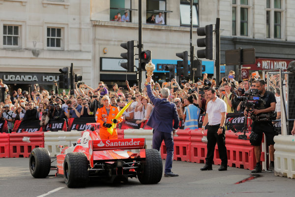 London, United Kingdom.  Wednesday 12 July 2017. Jenson Button, McLaren, gives a passenger ride to Naomi Campbell in the 2 seater and they pass Damon Hill with the British Grand Prix trophy. World Copyright: Zak Mauger/LAT Images  ref: Digital Image _54I2724
