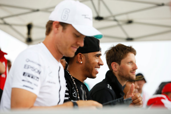 Hungaroring, Budapest, Hungary. Thursday 23 July 2015. Nico Rosberg, Mercedes AMG, Lewis Hamilton, Mercedes AMG, and Romain Grosjean, Lotus F1, sign autographs for fans. World Copyright: Charles Coates/LAT Photographic ref: Digital Image _J5R0488