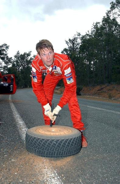 Marcus Gronholm (FIN) Peugeot knocks dirt from a wheel between stages.