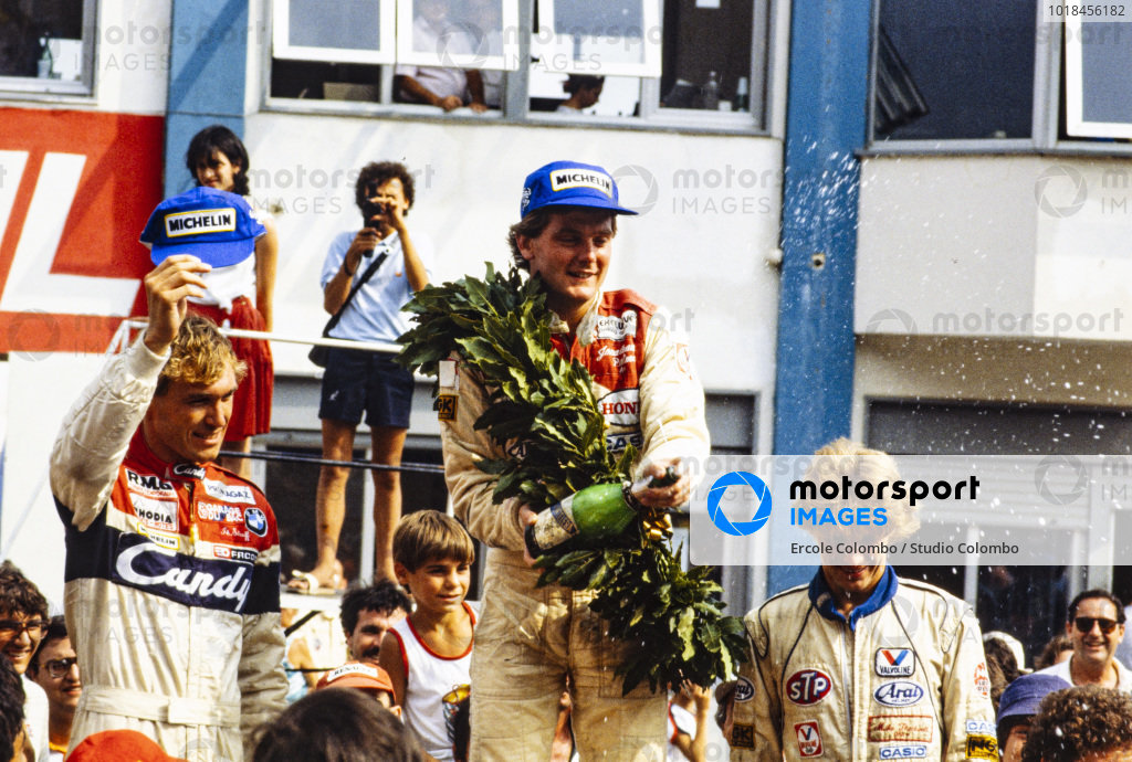 Jonathan Palmer, 1st position, Philippe Streiff, 2nd position, and Mike Thackwell, 3rd position, celebrate on the podium.