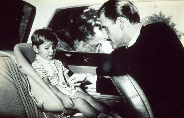 Graham Hill teaches his son Damon how to use  seatbelts. Formula One Drivers Childhood Photographs