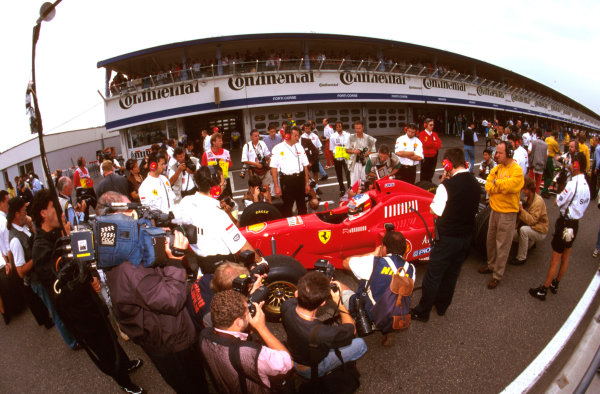Hockenheim, German.26-28 July 1996.Michael Schumacher (Ferrari F310) can't escape the eye of the worlds press at the end of the pitlane. Ref-96 GER 22.World Copyright - LAT Photographic