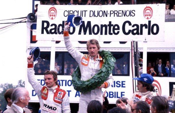 Jean-Pierre Jabouille celebrates victory on the podium with Gilles Villeneuve, 2nd position, and teammate René Arnoux, 3rd position.
