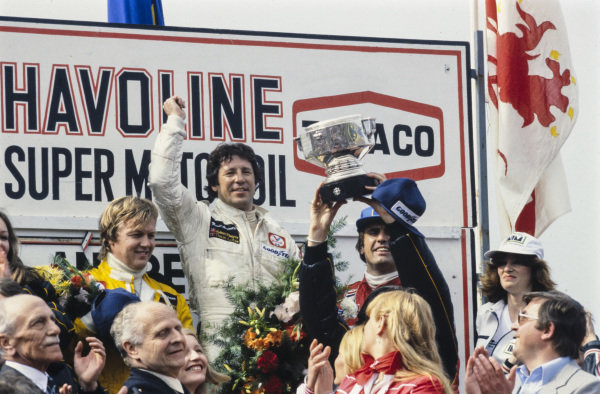 Mario Andretti celebrates victory on the podium with team mate and Ronnie Peterson, 2nd position, and Carlos Reutemann, 3rd position.