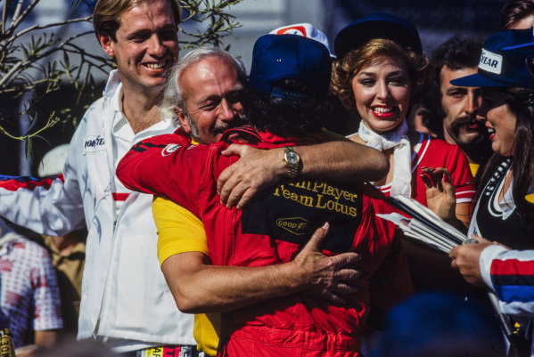 Colin Chapman hugs winner Mario Andretti.