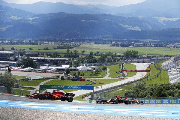 Charles Leclerc, Ferrari SF21, leads Sergio Perez, Red Bull Racing RB16B, and Daniel Ricciardo, McLaren MCL35M