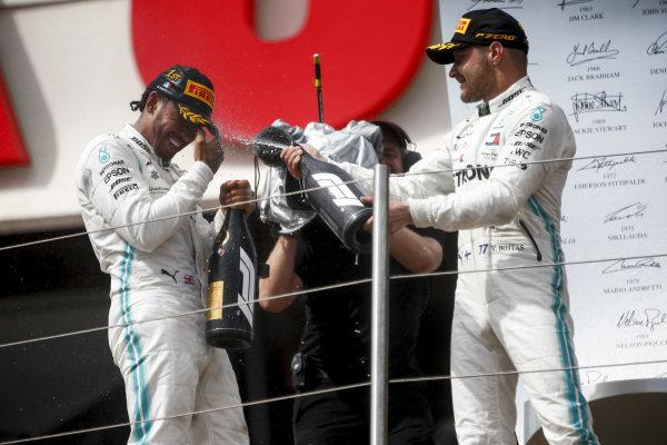 Valtteri Bottas, Mercedes AMG F1, 2nd position, sprays Champagne at team mate Lewis Hamilton, Mercedes AMG F1, 1st position, on the podium