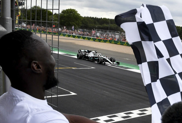 Stormzy, Rapper waves the finish flag while Lewis Hamilton, Mercedes AMG F1 W10 crosses the line