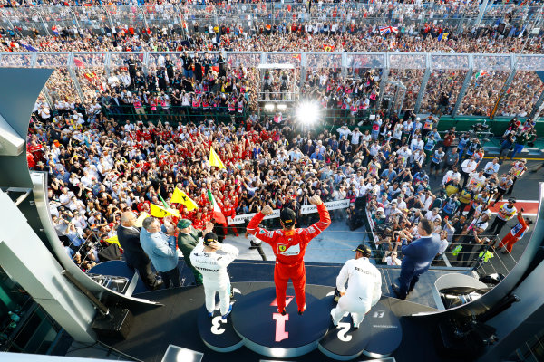 Albert Park, Melbourne, Australia. Sunday 26 March 2017. The podium men are cheered by the crowd. Race winner Sebastian Vettel, Ferrari, raises his arms, between Lewis Hamilton, Mercedes AMG, and Valtteri Bottas, Mercedes AMG. Sir Jackie Stewart applauds the drivers. World Copyright: Steven Tee/LAT Images ref: Digital Image _O3I3200