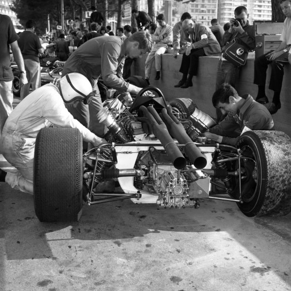 1966 Monaco Grand Prix. Monte Carlo, Monaco. 19th - 22nd May 1966.  Bruce McLaren (McLaren M2B Ford), retired. This was the team's debut Grand Prix, Tyler Alexander works on the car behind Bruce, portrait.  World Copyright: LAT Photographic. Ref: 34008.