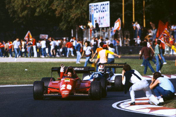 1983 Italian Grand Prix  Monza, Italy. 9-11 September 1983.  Ren? Arnoux, Ferrari 126C3, 2nd position, with helmet removed, leads Johnny Cecotto, Theodore N183 Ford, on the slow down lap as fans invade the track.  Ref: 83ITA13. World Copyright: LAT Photographic