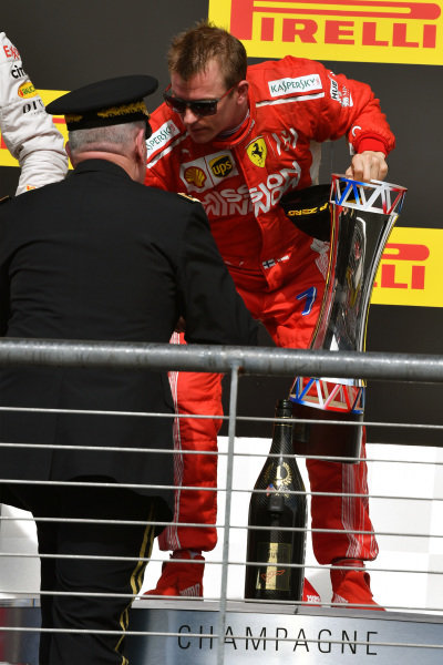 Kimi Raikkonen, Ferrari receives the winners trophy on the podium