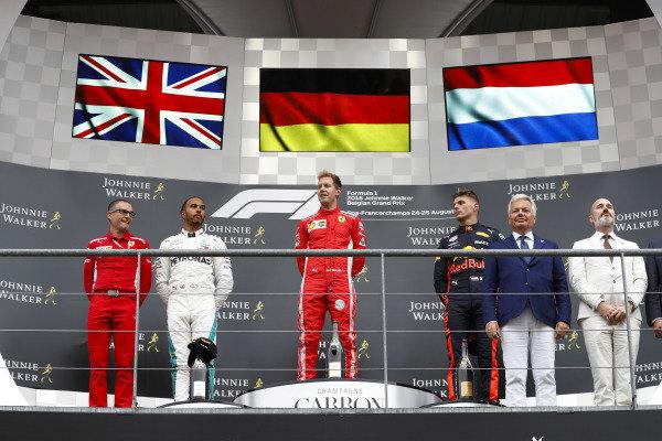 Winner Sebastian Vettel, Ferrari, celebrates on the podium, between Lewis Hamilton, Mercedes AMG F1, and Max Verstappen, Red Bull Racing.