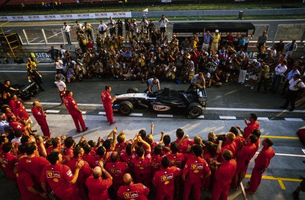 McLaren interrupts Ferrari's championship celebrations as mechanics push the car of Mika Häkkinen, McLaren MP4-16 Mercedes, down the pitlane.