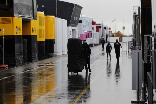 A Mercedes mechanic with a stack of tyres in the wet pit lane