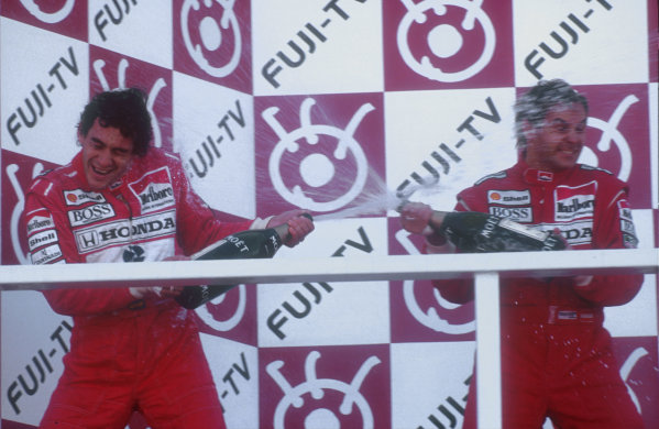 1991 Japanese Grand Prix.Suzuka, Japan.18-20 October 1991.Gerhard Berger celebrates his 1st position with teammate and newly crowned Formula One Drivers Champion Ayrton Senna, 2nd position (both McLaren Honda) as they dowse each other in champagne on the podium.Ref-91 JAP 20.World Copyright - LAT Photographic