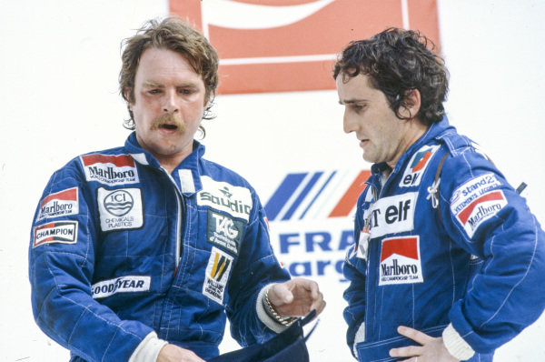 Keke Rosberg, 2nd position but later disqualified, and Alain Prost, 3rd position but eventually awarded the race win, on the podium.