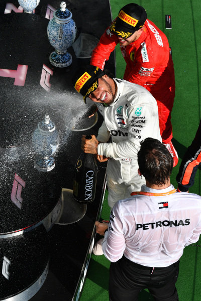 Sebastian Vettel, Ferrari, 3rd position, blasts Lewis Hamilton, Mercedes AMG F1, 1st position, with Champagne on the podium