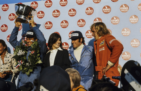Carlos Reutemann celebrates victory on the podium with Carlos Pace, 2nd position, and James Hunt, 3rd position.