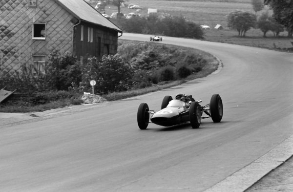Jim Clark, Lotus 25 Climax, gives a signal as he drives by.